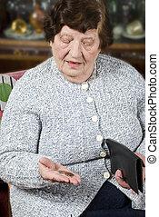 Pensioner counts her last money - Elderly pensioner sitting...