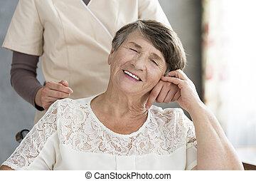 Pensioner holding hand of nurse