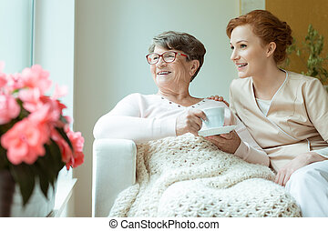 Happy pensioner with glasses and cup of tea looking out the window with her caucasian caretaker