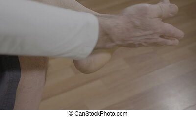 Pensioner man relaxing himself with reflexotherapy feet massage at home