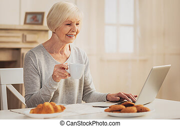 Pensioner smiling while watching family photos on laptop