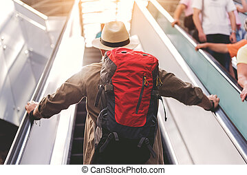 Pensioner standing on escalator in airport