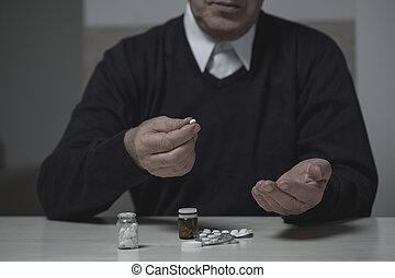 Pensioner taking pills - Horizontal view of male pensioner ...
