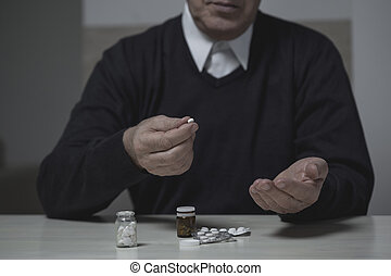 Pensioner taking pills - Horizontal view of male pensioner...