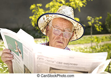Pensioner with newspaper - Old man with reading glasses and ...