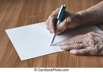 Pensioner writes in pen on paper.