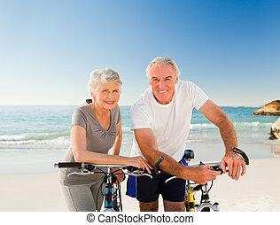 pensioneratt par, med, deras, cyklar, stranden