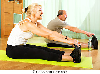 Pensioners doing exercises indoor - Active pensioners doing...