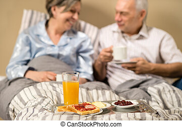 Pensioners drinking coffee in the bed
