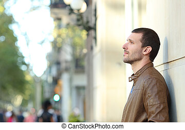 Pensive adult man looking away in the street