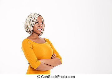 Pensive african american woman with arms crossed and looking up