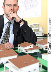 Pensive architect sat with model housing project