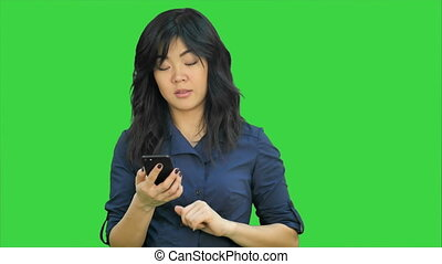 Pensive asian businesswoman reading presentation on smartphone, looking at camera on a Green Screen, Chroma Key