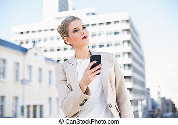 Pensive attractive businesswoman sending a text message