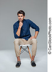 Pensive attractive casual young man sitting on chair over...