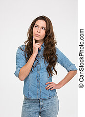 Pensive attractive young woman standing and thinking