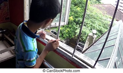 Pensive autistic boy child looking through a hospital window