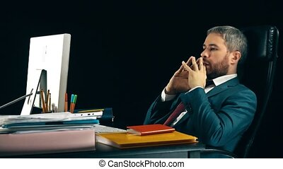Pensive bearded businessman swinging on his office chair....