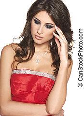 Pensive beautiful brunette woman in red dress
