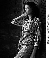 Pensive beautiful loneliness woman in trendy black and white checkered shirt thinking about destiny on wooden doors background in dark and looking. Short hairstyle.