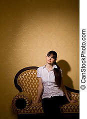 pensive beautiful young woman brunette woman sitting on sofa in room