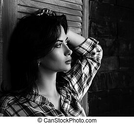 Pensive beautiful young woman profile in trendy black and white checkered shirt thinking about destiny on wooden doors background and looking. Closeup black and white portrait. Art