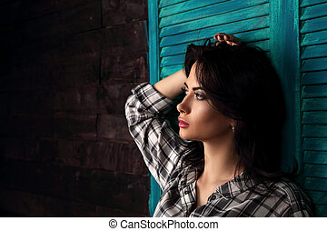 Pensive beautiful young woman profile in trendy black and white checkered shirt thinking about destiny on blue wooden doors background and looking. Closeup portrait