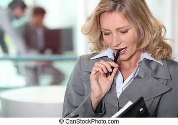 Pensive blond businesswoman chewing on pen