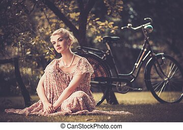 Pensive blond retro woman in summer dress sitting on a meadow