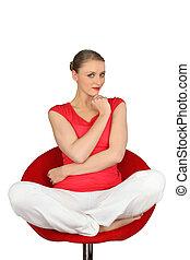 Pensive blond sat cross-legged on swivel chair