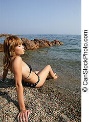 Pensive blond woman sat on beach