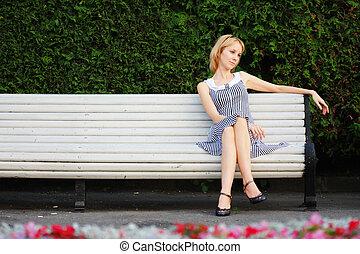Pensive blonde sitting on bench