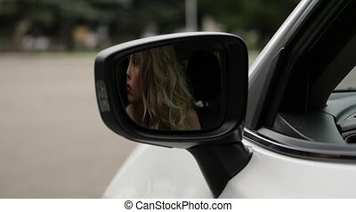 pensive blonde woman sitting at the wheel of a car and...