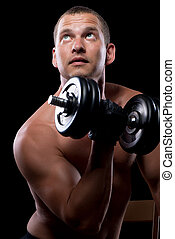 pensive bodybuilder while training with dumbbells