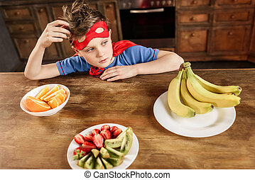 pensive boy in red superhero costume sitting in kitchen with fruits