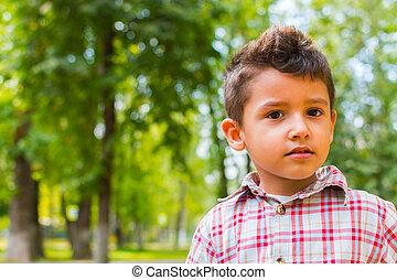 pensive boy in the forest background