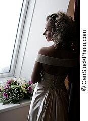 Pensive bride by window