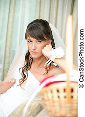 pensive bride in a white dress looking at camera