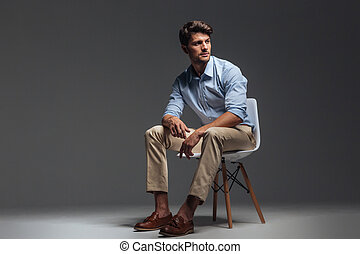 Pensive brunette man in blue shirt sitting on the chair