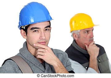 Pensive builder with young intern