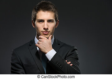 Portrait of pensive man wearing business suit and black tie touches his face