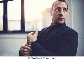 Pensive businessman against the window in a modern office