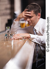 Pensive businessman having drink in classy bar. young man...