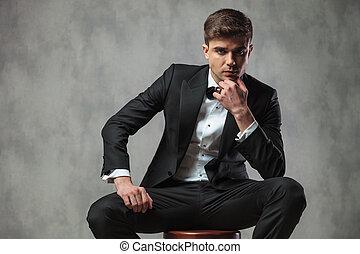 pensive businessman in black tuxedo sitting on chair