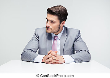 Pensive businessman sitting at the table