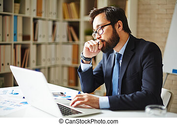 Pensive businessman sitting in front of laptop in office