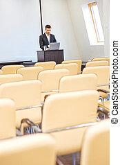 Pensive businessman standing and using laptop in empty meeting hall