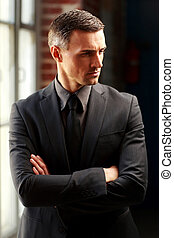 Pensive businessman standing with arms folded
