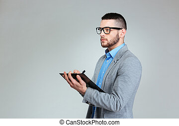 Pensive businessman standing with clipboard
