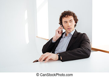Pensive businessman talking on the phone